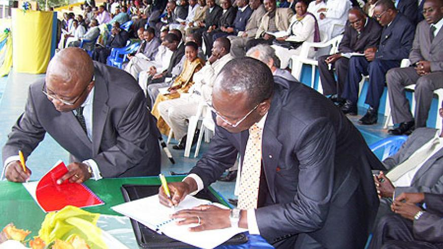 The Rector of IPB Prof Nyombayire (R) and Dr. Jean Emmanuel Djomo sign a memorandum of cooperation at Gicumbi stadium on Friday. (Photo; A.Gahene)