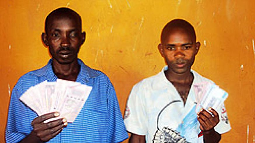 Samuel Hakizimana and James Gasirikare display the fake notes while under police custody. (Photo by S. Rwembeho)