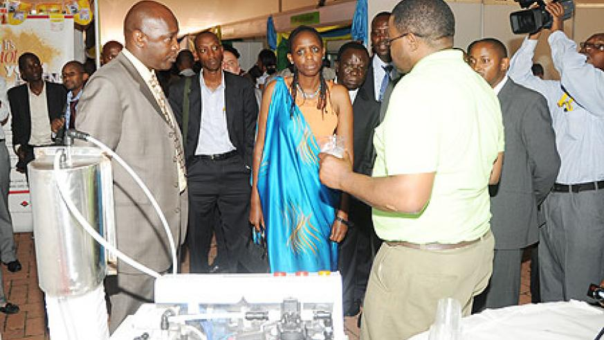 The Minister of Agriculture Dr. Agnes Kalibata viewing the milk dispenser machine at the 6th ESADA Exhibition. Right is Antonio Magnaghi of Lattebox. (Photo; J. Mbanda)