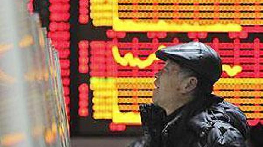 An investor checks stock information with a computer at a brokerage house in Hefei, Anhui province February 20, 2012. China shares ended up 0.3 percent on Monday .