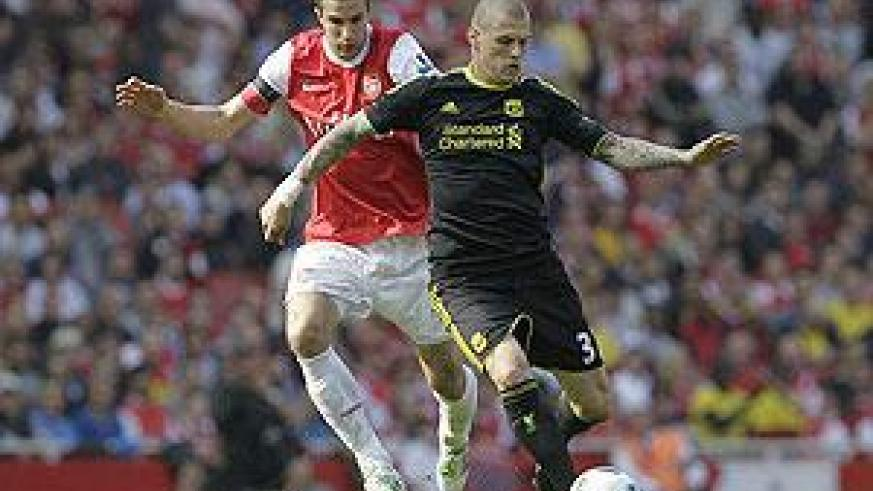 Liverpool defender Srktel holds off Arsenal star striker Robin van Persie. The two will be at it again this afternoon.  Net photo.