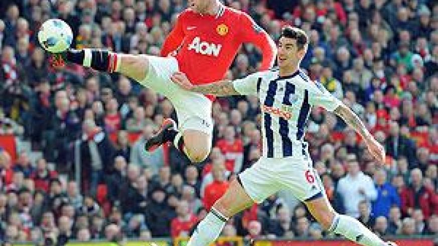 Wayne Rooney (L) vies for the ball with West Brom's Liam Ridgewell during the English Premier League football match yesterday. Net Photo.