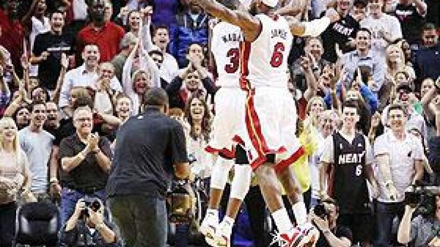 Dwyane Wade (3) and LeBron James leap in the air to celebrate the Heat's 93-91 overtime win over the Pacers in Miami. Net Photo.