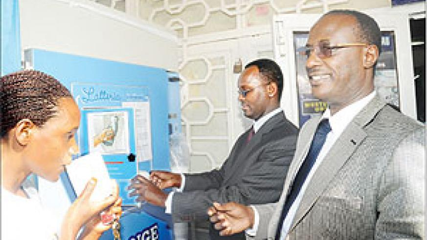 Inyange Industries Chairman prof. Mannaseh Nshuti (R) and the Permanent Secretary in the Ministry of Trade and Industry Emmanuel Hategeka serve milk from a public dispenser after its launch in Remera on Thursday. The New Times Times / File.