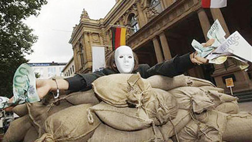A protester holds fake money next to a wall of sandbags built during a protest against financial speculation in Frankfurt stock exchange June 17,2012. Net photo.