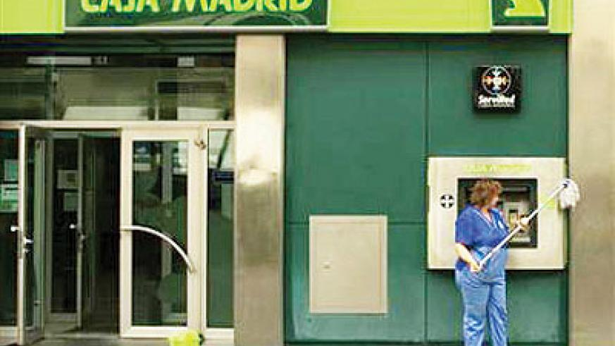 A cleaner cleans the facade of a Bankia-Caja Madrid bank branch in the Andalusian capital of Seville June 25, 2012. Net  photo.