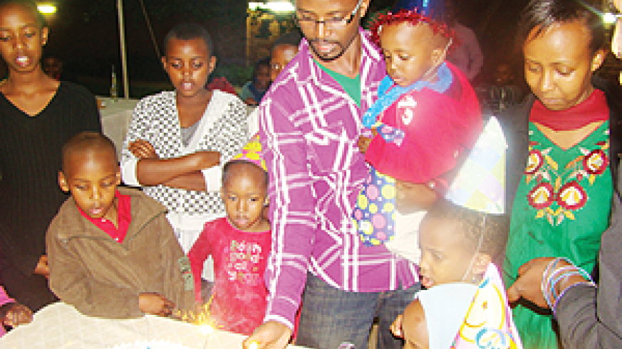 Cyusa's Dad (L) and mummy (R) help him to cut the cake.
