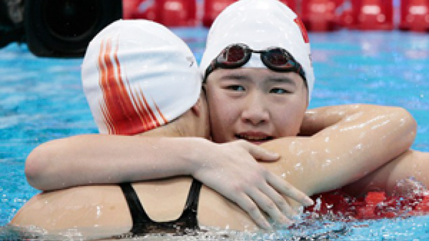Ye Shiwen hugs Xuanxu Li after her victory at the Aquatics Centre at the Olympic Park. Net photo.
