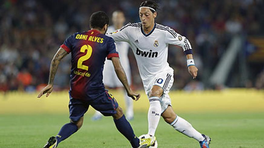 Barcelona's Daniel Alves (L) duels for the ball with Real Madrid's Mesut Ozil during the La Liga match at the Camp Nou Stadium. Net photo.