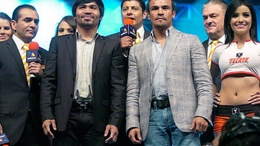 Pacquiao, left, and Marquez, right, pose for photos during a news conference, Wednesday. Net photo.