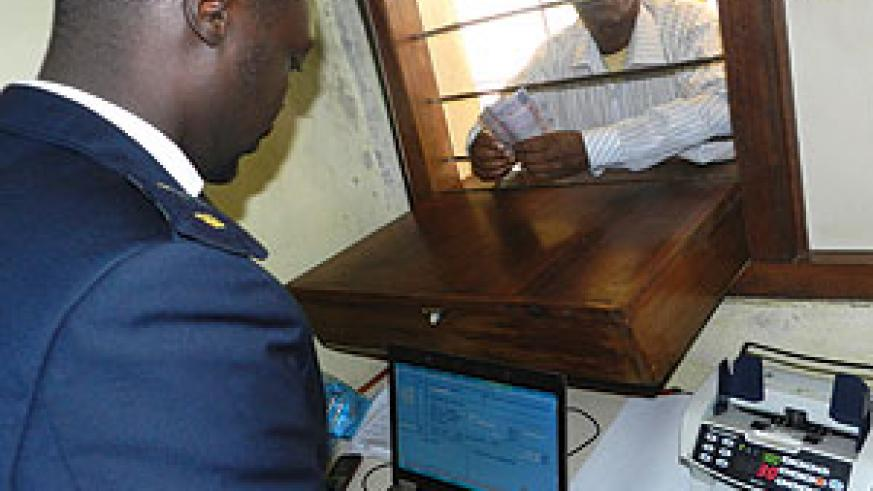 A trader pays tax at a customs point at Rusumo border. Tanzania and Rwanda have agreed to support small cross-borders traders. The New Times/ Stephen Rwembeho