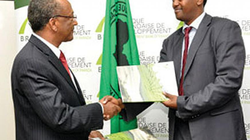 Kayonga and Negatu Makonnen, the AfDB country chief exchange the $8m funding deal documents earlier this week.