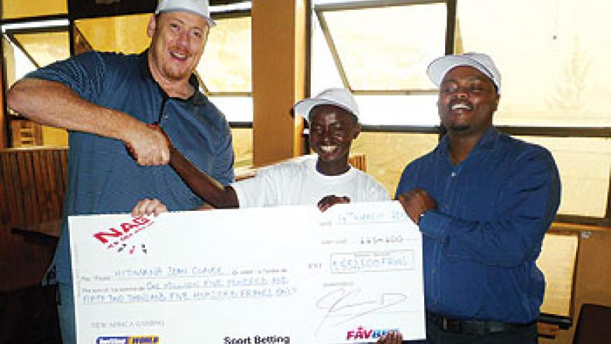 A sports betting winner receives a dummy cheque from New Africa Gaming officials last week. The New Times/J. Mbanda