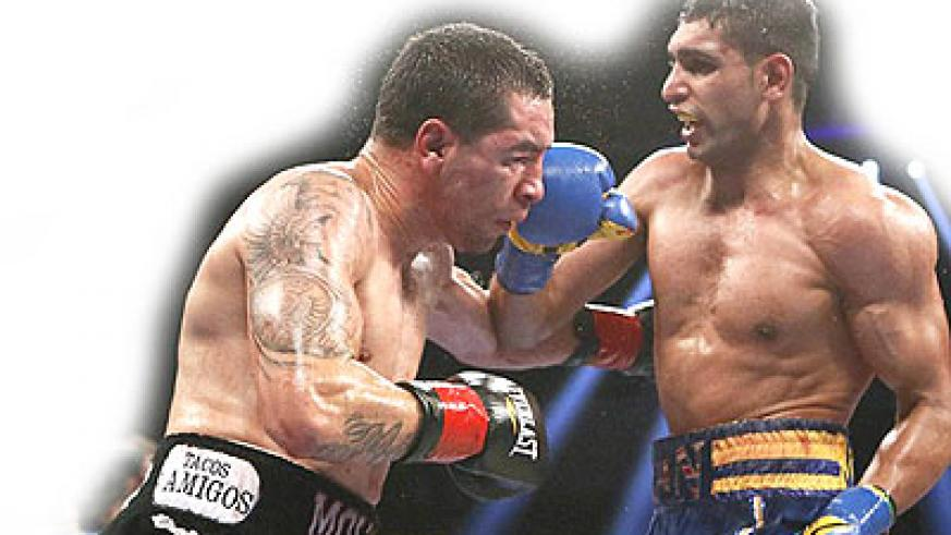 Amir Khan (right) forced Carlos Molina to retire at the end of the 10th round last December. Net photo Net photo.