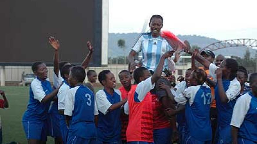 The AS Kigali coach is carried shoulder high  by her players after winning the women soccer league title. Sports Magazine / T. Kisambira.