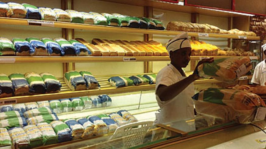 A worker packing bread at a store in town. The prices of bread are bound to rise as bakers try to cover operations costs. The New Times / Peterson Tumwebaze