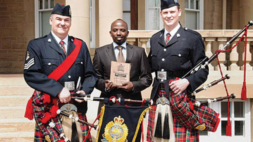 Muganga (middle) poses with his award. The New Times / Courtsey photo