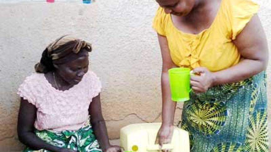 Mukarutwaza prepares to discant Sur'Eau into a jerrycan, and left, she shares the clean water with her neighbour, Mukashema. The New Times/ Courtesy.