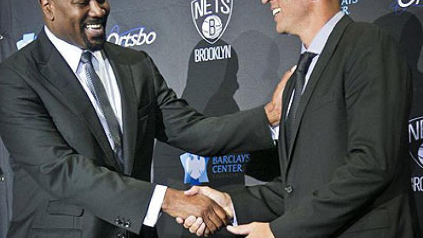 Brooklyn Nets general manger Billy King, left, shakes hands with new coach Jason Kidd after an NBA basketball news conference introducing Kidd Thursday.  Net photo.