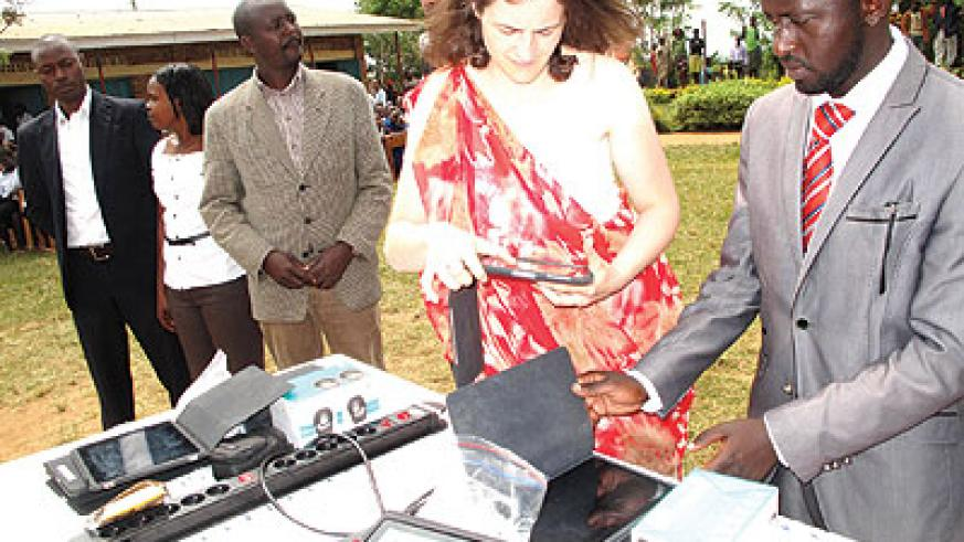 Jenny Oakley hands over the iPads to school head teachers. The New Times / Stephen Rwembeho.