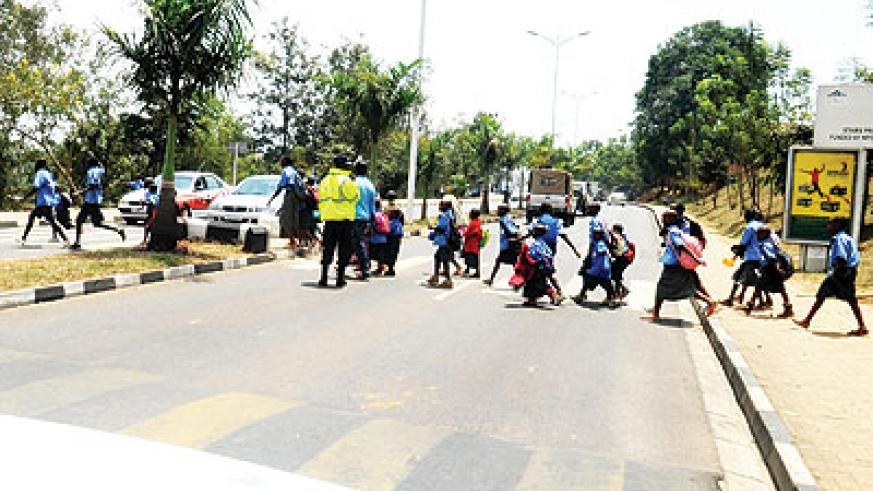 Traffic officers help school children to cross a busy road.  The New Times/ T. Kisambira.