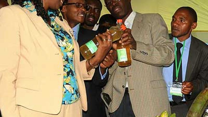 Dr. Kalibata (L) and other officials examine bottles of banana juice during the conference in Kigali yesterday. The New Times/John Mbanda