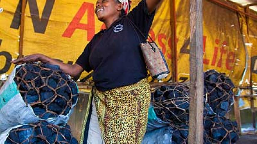 A woman at her charcoal vending stole in Kigali. Police have cautioned charcoal burners in Bugesera District against illegal felling of trees.  The New Times/ File.