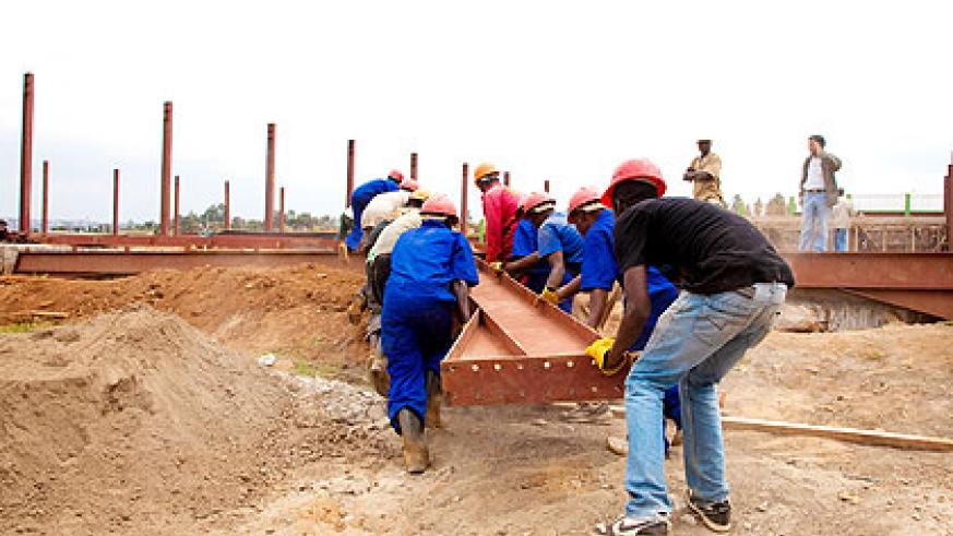 Workers carry metal frames at a construction site. The New Times/ T. Kisambira.