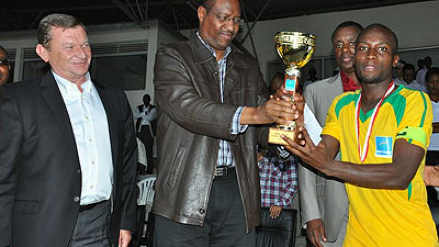 <p>The Minister of Sports and Culture Protais Mitali giving the Super Cup trophy to AS Kigali captain Jimmy Mbaraga yesterday. Looking on Babil Group's Head of International ....