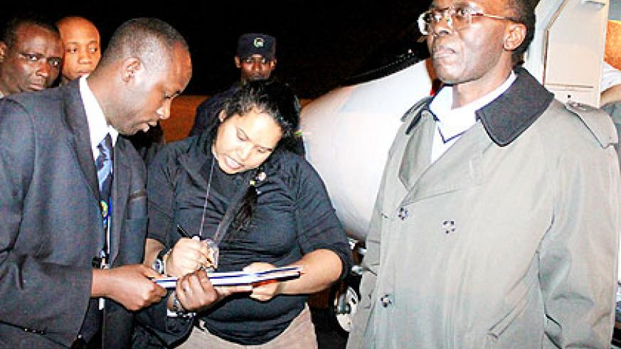 Officials clear the formalities for the extradition of Mugesera at Kigali International Airport. The New Times/ File.