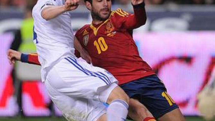 Cesc Fabregas (R) of Spain is tackled by Joona Toivio of Finland during the FIFA 2014 World Cup Qualifier at estadio El Molinon. Net photo.