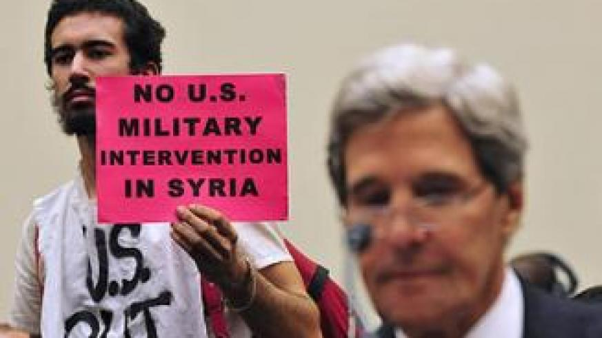 A protester holds a banner as U.S. Secretary of State John Kerry testifies in a House of Representatives hearing about Syria on Capitol Hill in Washington Sept. 4, 2013.. Net photo.