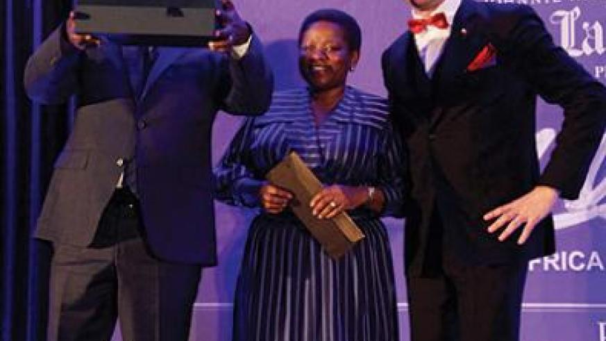 Gatera displays the AABLA (East Africa) award. Other three people also won in various categories. The New Times / John Mbanda