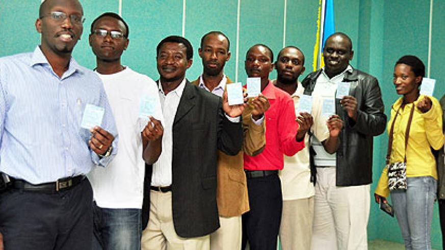 Rwandans in India proudly show off their voter's cards as they queue to choose their parliamentary candidates yesterday.  The New Times/ Courtesy.