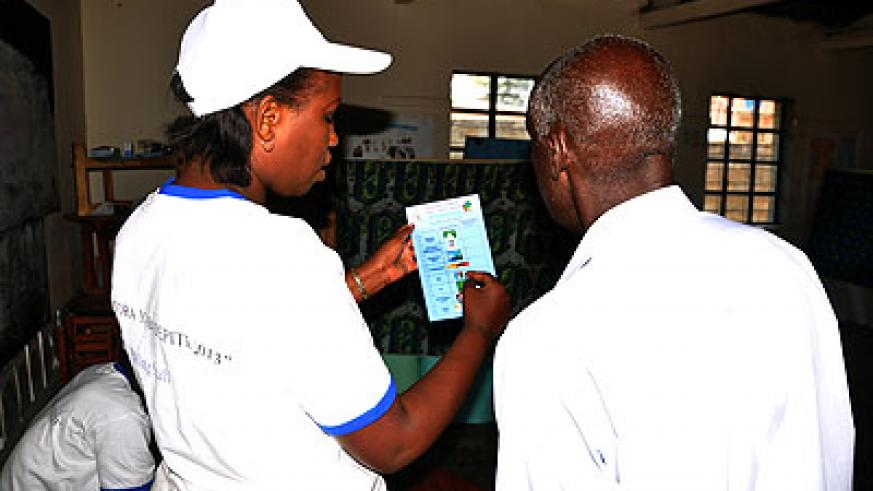 A returning officer guides an elderly man at polling station in Kigali. The New Times/John Mbanda.