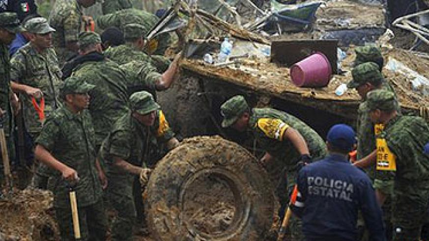 Rescuers search for survivors of a landslide which buried a bus in Altotonga. Net photo.