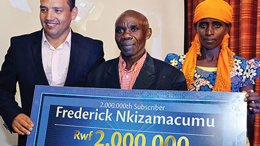 Nkizamacumu (middle) receives a Rwf2m dummy cheque flanked by his wife and Camberos. The New Times/Ben Gasore