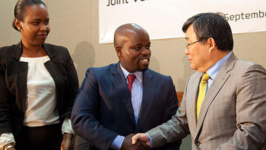 Minister Nsengimana (C) and Kim seal the deal with a handshake as RDB's Akamanzi looks on. The New Times/T. Kisambira