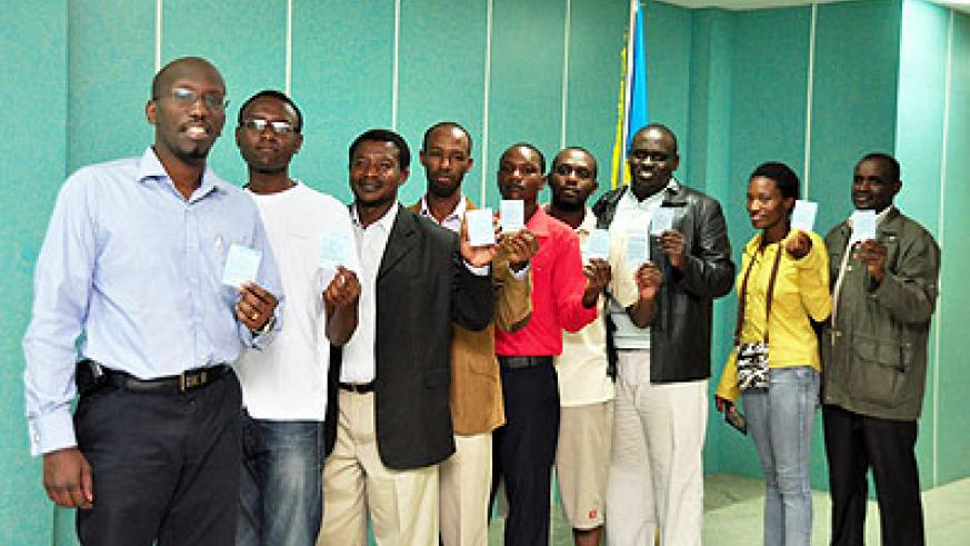 Rwandans in New Delhi, India,   proudly show off their voter's cards before voting on Monday.    The New Times/Courtsey.