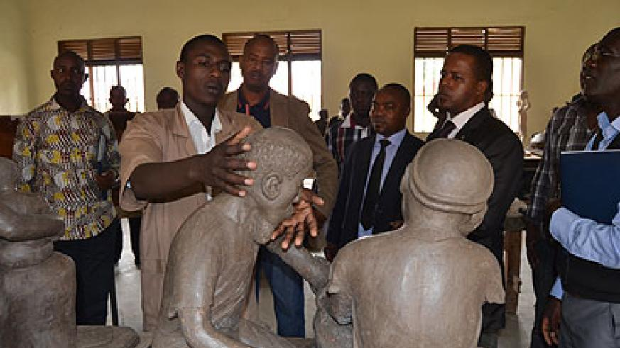 Thomas Mvugirende, one of the candidates showing State Minister and other WDA officials his sclupture. The New Times J Mbonyinshuti