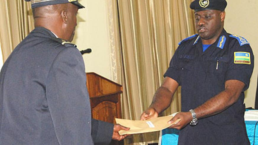 IGP Gasana (R)gives a certificate of merit to one of the participants.   Saturday Times/. Rwembeho.