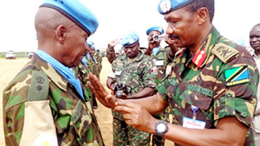 An RDF peacekeeper (L) is decorated during the ceremony on Saturday. The New Times/ Courtesy.