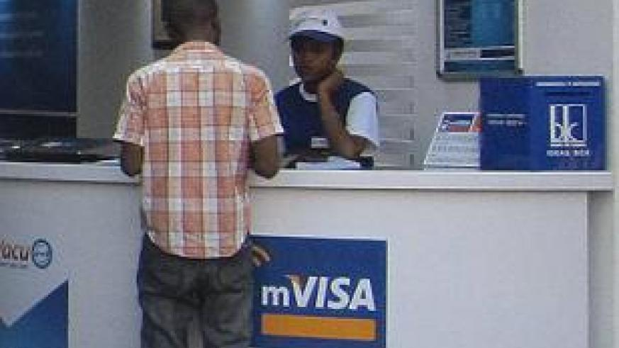 A customer being served at a Bank of Kigali mVisa agency. mVisa helps rural areas to access financial services. The New Times / Ben Gasore