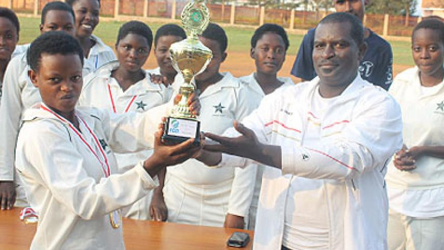 Emmanuel Bugingo, the Director Sports in the Sports ministry hands over the trophy to IPRC captain Josée Marie Muhoza. The New Times / Courtesy.