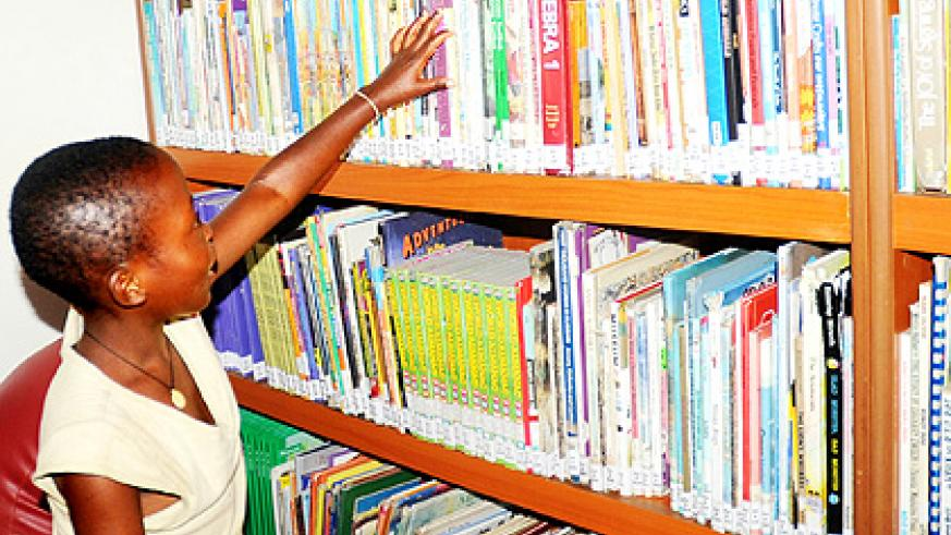 A pupil selects books from a shelf. Reading culture is improving The New Times/ File.