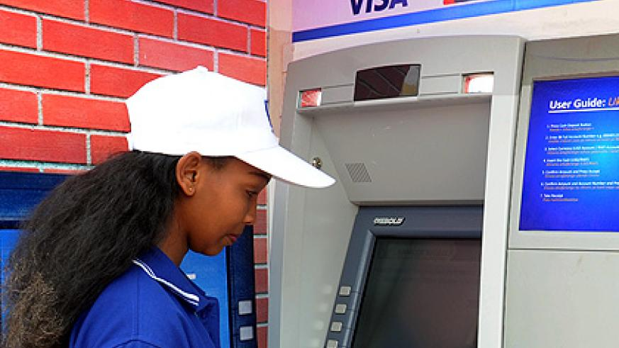 A bank client transacts from an ATM booth in Kigali. Cards are replacing papers. The New Times/ File.