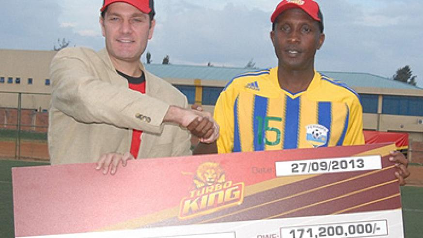 Bralirwa's Marketing Director Jan Van Velzen and FA boss Celestin Ntagungira displaying the Turbo King dummy cheque on Friday. Times Sport/Courtesy