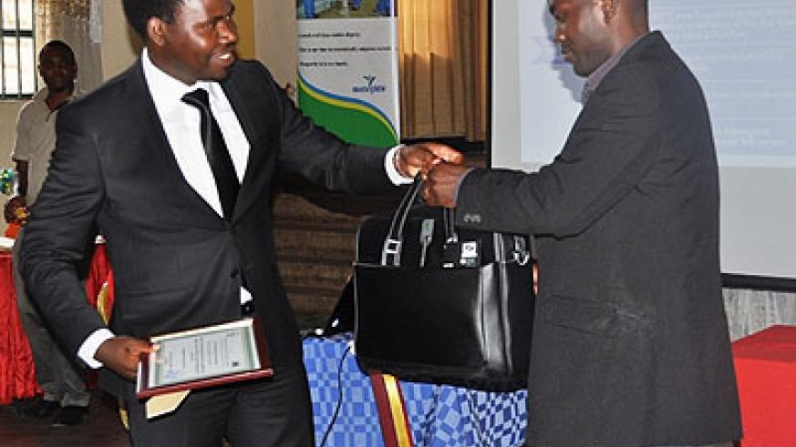MP Bamporiki (L)recognises one of the best performers with a  certificate and laptop.   The New Times/ Susan Babijja.