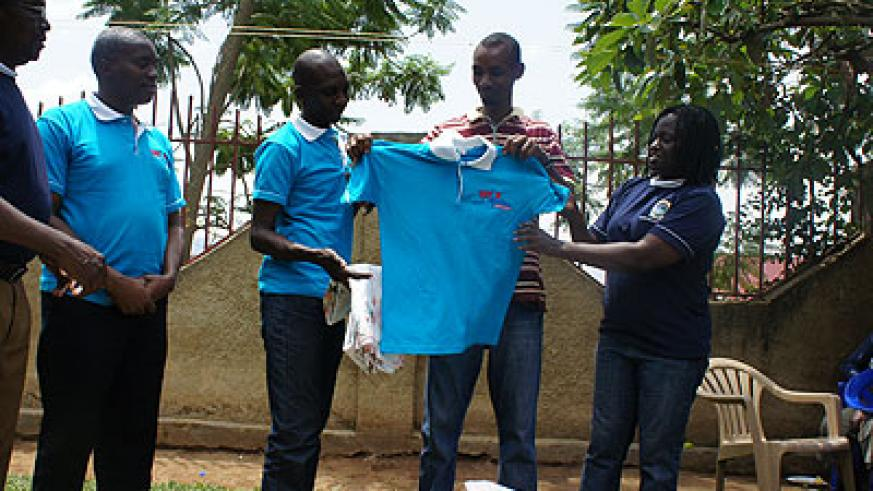 Ruzindana receiving some clothes for the children donated by Mount Kenya University lecturers. The New Times/E. Kabeera