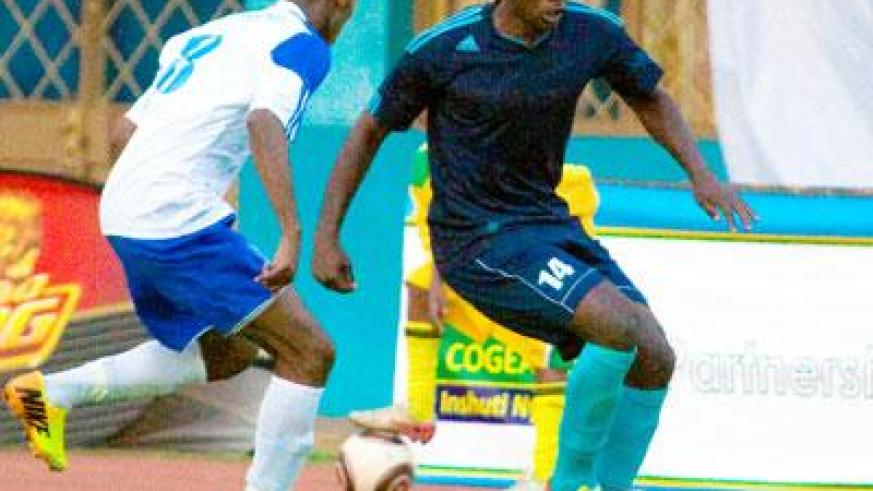 Police's striker Kipson Atuheire attempts to strike past Rayon Sports' Djamal Mwiseneza in yesterday's match at Amahoro stadium. Sunday Sport/T. Kisambira